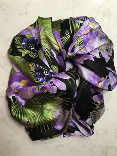 "Fabric: silk 100%.  Vibrant purple and green hues on a black background. Hand made. Measurements of a scarf is 59"" long and 22"" wide I recommend hand-washing only, in lukewarm water with a gentle cleanser. Do not rub, do not wring! Mop it gently in a towel.Iron in middle setting when slightly wet. Iron on the reverse side! The scarf is made for the individual who prefers to wear one-of-a-kind. It is great for every season to wear with any of your favorite clothing."
