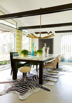 These black-painted beams frame a dining room scene that's centered around a golden chandelier and large-scale animal-print rugs.