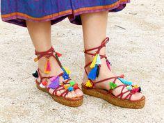 Sandalias griegas con flecos y adornos multicolor. Agarres de antelina roja. Suela de plataforma.