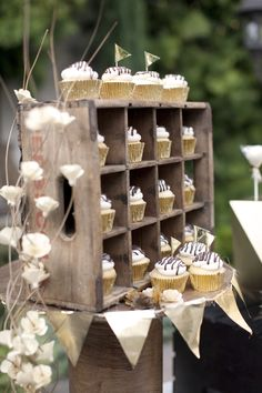 I love how this cupcakes are displayed. Another shot of our (cup)cake table. We used a vintage soda crate to house individual cupcakes, handmade the banners and flags, and used twigs and flowers made out of thin wood chips for accents. Cupcake Stand Wedding, Cake And Cupcake Stand, Cupcake Display, Wedding Cupcakes, Cupcake Cakes, Rustic Cupcake Stands, Cupcake Table, Rustic Wedding, Our Wedding