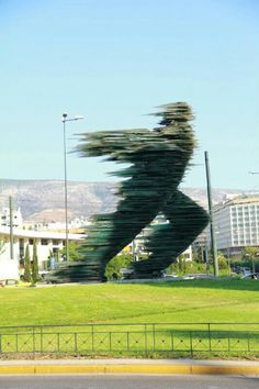 """The legendary sculpture """"The Runner"""" is located in Athens since 1988. It is made entirely of dark green glass. The author of this unusual sculpture is the Greek sculptor COSTAS VAROTSOS."""