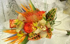 Tropical bridal bouquet of birds of paradise, orchids, pin cushion protea, circus roses and croton leaves designed by Flowers by Fudgie
