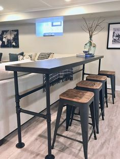 A HGTV fixer Upper basement remodel with shiplap wood walls, sliding barn doors, and industrial chic accents. We made a long counter height for behind the bar and add rustic black and wood stools from Raymour & Flanigan.