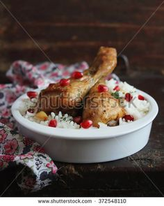 Roasted chicken legs with rice and pomegranate seeds, selective focus