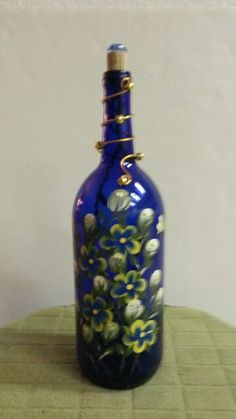 This large cobalt blue wine bottle luminary sports hand-painted Plumeria blossoms along with whimsical butterflies. Its really accented when