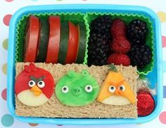 The Angry Bird characters are sitting upon a stacked sandwich and are made using dyed provolone cheese, cheddar, icing eyes and cucumber peel.