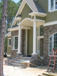 Good stone and siding mixture - but use hardi board instead of siding and run a brick line at the bottom to continue brick down the sides and back from the slant elevation in back.