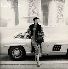 Model in front of Mercedes, wearing tweed dress, matching coat with fur collar, fur hat, and gloves (all by Patou), holding handbag, with L'Arc de Triomphe in background, 1955