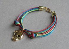 Pulseira de fios colorido com pingente de caveira e fecho folheados. R$32,00
