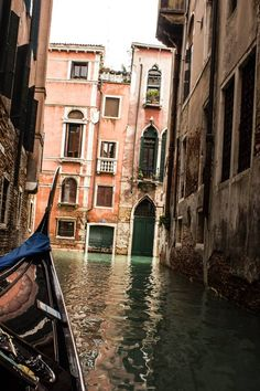 A gondola glides silently along a lonely canal in Venice.