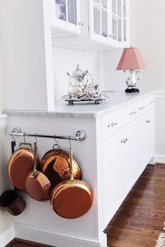 3. Hook and Hang Your Pots We often see pots and pans hung on hooks on kitchen walls or from a pot rack over the island, but sometimes that storage solution just doesn't go with a home's aesthetic. We love the idea of your most-used pots and pans from a bar on the side of your kitchen cabinets; since they're not at eye level, they're discreet, yet still handy.