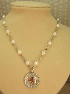 I've always enjoyed the jewelry made by Tamara Berg.  She uses pearls, real gem beads, and vintage style to combine hallmarked English fob medals into interesting necklaces and bracelets.