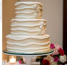A white swirl floral motif accented each of the fondant-covered tiers, which were chocolate with raspberry filling, French vanilla with strawberry filling, and mango with mango puree.