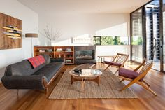dark grey smooth lined sofa accompanied with wooden chairs with simple red cushion of The Simplicity of Mid-Century Modern Sofa that Survived Half Decade