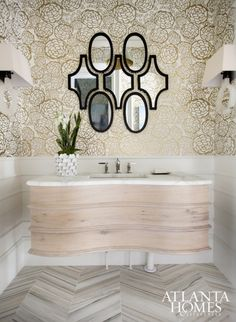 2015 Decorators' Show House & Gardens | Beth Kooby strived for a modern interpretation of classic French design in the powder room. An arrangement of mirrors, metallic wallpaper and marble flooring allow the white oak, serpentine-shaped vanity to shine.