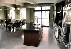 Kitchen with granite countertops and Viking appliances, including a six-burner range. There's also a built-in wine chiller and a breakfast bar. Concrete floors and floor to ceiling windows in a condo with a contemporary and industrial style.