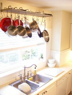 Creative repurposing of a hat/ shoe rack. Hung above the sink, it becomes a nice pot rack—and lids fit perfectly on top.
