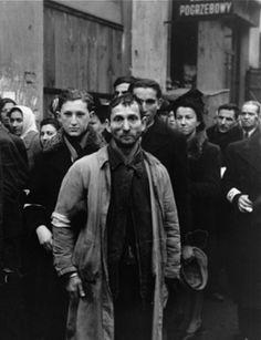 Regards sur les ghettos au Mémorial de la Shoah : Groupe d'hommes juifs ôtant leur chapeau devant le photographe allemand. Ghetto de Varsovie, été 1941. - Photographie Willy Georg. © USHMM