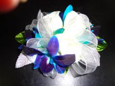 Wrist corsage of white Spray Roses and blue Dendrobium Orchids. Designed by China Rose Florist, Marco Island, Fl.