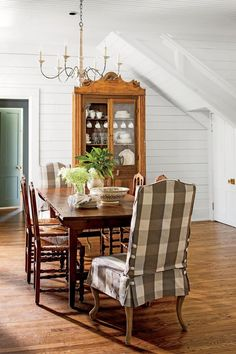 Farmhouse style dining room with buffalo check slipcovered chairs and vintage dining cabinet in cottage with white shiplap. Rachel Halvorson Inspired Decorating Tips. #diningroom #farmhouse #shiplap #interiordesign
