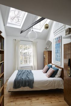 This eclectic bedroom feels bigger with the roof windows. The roof windows add natural light and makes rooms feel more open and spacious.