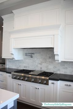 white kitchen. marble tile backsplash. black countertops. love the hood style too.