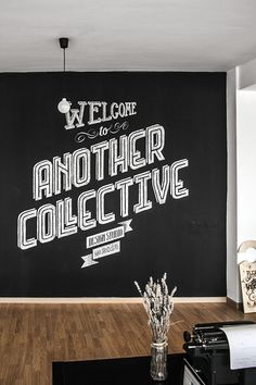 """The wall here presented aims to be a mark of our identity. By using chalk and white pastel pencil, the typography composition wants to give a warm reception to everyone that visits Another Collective, quoting """"Welcome to Another Collective 