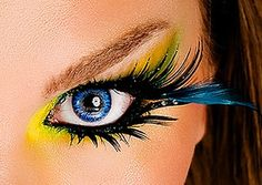 Extravagant yellow eye makeup with false eyelashes and blue feather accent onto the outer corners