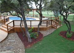 Mix and match colors and textures to bring together the varying designs a raised pool can bring to your landscape. The wooden lines of this deck is well balanced by flower bed borders and gracefully draping tree canopies.