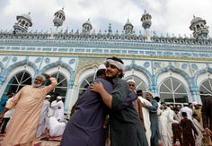 Men greet each other after attending Eid al-Fitr prayers at Jamia Masjid in…