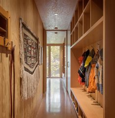 A hallway with a custom-built shelving that doubles as a mudroom.