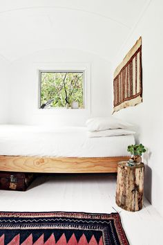 """The bed was found and bought on Trade Me (a New Zealand version of eBay) before we flew in to do-up the space, the rug is a vintage Afghan carpet, the artwork above the bed is an old bark tapa cloth from Papua New Guinea, the suitcase belonged to Andrew's grandfather, and Andrew found the log on the property which we then turned into a bedside table/stool.""  handwriting1"