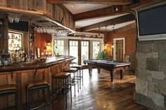 What a great entertainment room! The shelving behind and beneath the bar was crafted of reclaimed pine, and remains unfinished, adding to the bar's rustic charm. Bar Pool Table, Pool Table Room, Pool Tables, Basement House, Basement Pool, Basement Ceilings, Basement Bars, Walkout Basement, Basement Bar Designs