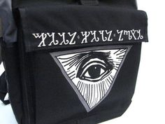 A close up of the graphic of an all seeing eye and thebian alphabet on a medium waterproof rolltop backpack.