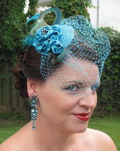 Peacock blue satin flowers, Russian  veil & peacock feathers. The bling is dark aurora borealis beads. What a dramatic statement for a bride! $120