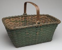 """VIRGINIA PAINTED WHITE OAK SPLINT MARKET BASKET, VIRGINIA PAINTED WHITE OAK SPLINT MARKET BASKET, rectangular form with low arched handle, wrapped rim, step-woven handle supports, slightly open weave bottom, outstanding original dry green paint with excellent patina. Collected in the northern Shenandoah Valley. Fourth quarter 19th century. 14"""" h, 13"""" x 19 1/2"""" rim. $750, 06-28-2008, Green Valley Auctions."""