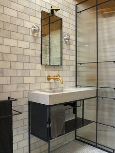 Flor basin installed in a residential bathroom in London. The basin has an extended vanity area which has been used as a shelf through the shower screen,