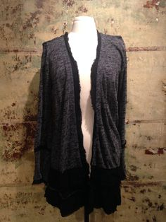Heathered grey and black high-low cardigan with black ruffled detail throughout. A cozy and chic throw on for the chilly fall months, you won't want to take it off!