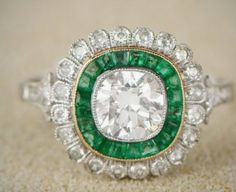 A gorgeous handcrafted diamond and emerald floral halo engagement ring featuring a lively old mine cut diamond. A halo of French-cut emeralds encircle. Floral Engagement Ring, Halo Engagement Rings, Vintage Engagement Rings, Vintage Art Deco Rings, Diamond Dreams, European Cut Diamonds, Art Deco Jewelry, Diamond Are A Girls Best Friend, Antique Jewelry