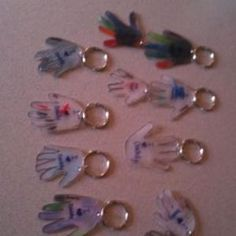 Key chains the daycare kids can make. Made from shrinky dink paper/plastic found in any craft store. Put a hand print on the paper and write a message in the hand. Pop it in the oven and you have miniature hand keychains. Great Mother's/Father's Day present :) by jean