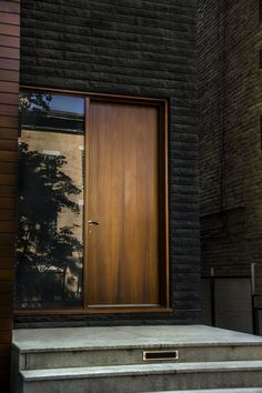Dark bricked wall with wooden door constrast  ITCHBAN.com // Architecture, Living Space & Furniture Inspiration #10