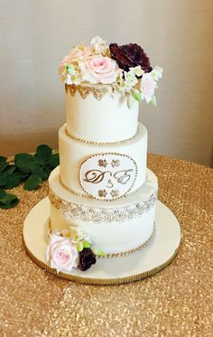 Wedding cake, purple and pink flowers, gold trim, gold initials, off white and gold