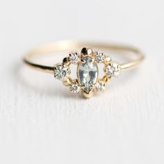 Handmade Through the Mist Ring by Melanie Casey is now available with a mossy green marquise sapphire center stone surrounded with a cluster of tiny white diamonds!
