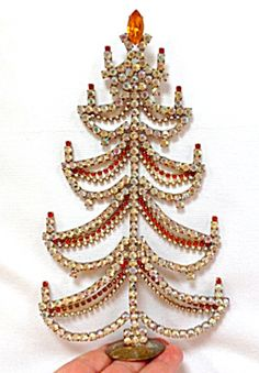 AB Red Crystal Rhinestone Vintage Christmas Tree Village Decoration (Image1)Czech glass self-standing Christmas Tree that is dripping with sparkling rhinestones. The rhinestone colors are mostly AB wash with ruby red garland and 'candle flames'plus gold-citrine topper. There are also tiny strands of pearl 'garland' under the red. 7 1/2 inch tall.