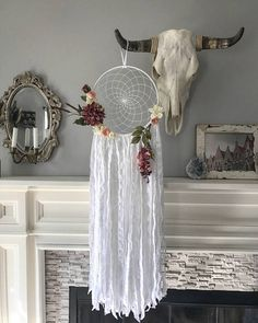"""Dahlia Dream Catcher. The Dahlia dreamcatcher is an elegant and beautiful wall hanging. The web is lovingly hand woven in white thread, perfectly blending with the white fabric tightly spun around the ring. The ring is 12"""" in diameter, and from it hangs gorgeously tattered looking white cloth. The ring is accented with stunning faux flowers and greenery, in various shades of cream, dusty rose, and pink. 