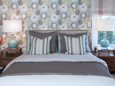 Modern yet warm and feminine, this bedroom features whimsical floral wallpaper that distracts from the window creeping into headboard wall. To allow for more storage and keep the space streamlined, custom-designed bedside tables float on the wall.
