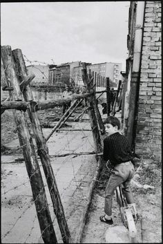 A boy on a bike watches as East German soldiers build the Wall between East and West Berlin. 1965