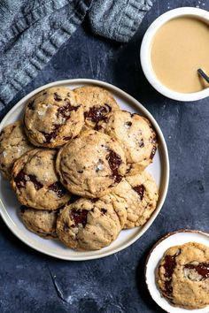 Chewy vegan tahini chocolate chip cookies on a plate with a bowl of tahini in one corner and a cookie served on a small plate in another