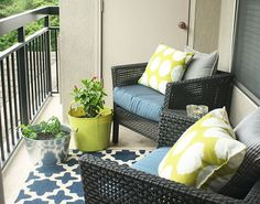 Don't kick these buckets--they're pretty, and besides, they're holding herbs on blogger Jewel Hazelton's small patio. How clever to match the colors of her container to her pillows, and echo the blue seat cushions with a rug! Click on for more small garden design tips!