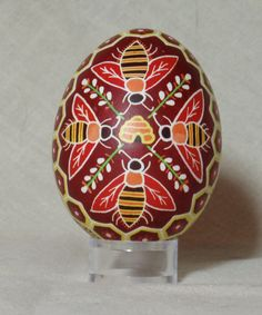 Original design of bees surrounding a hive with honeycombed border full of flowers on a deep red background. The shell is from a friends pet duck, and slightly larger than a chicken egg. Shown next to chicken egg pysanka of similar design for size comparison. Contents removed through a single hole on the top (shown). Finished with multiple coats of Golden MSA varnish for superior archival-quality protection. Ships with a clear lucite stand for display.